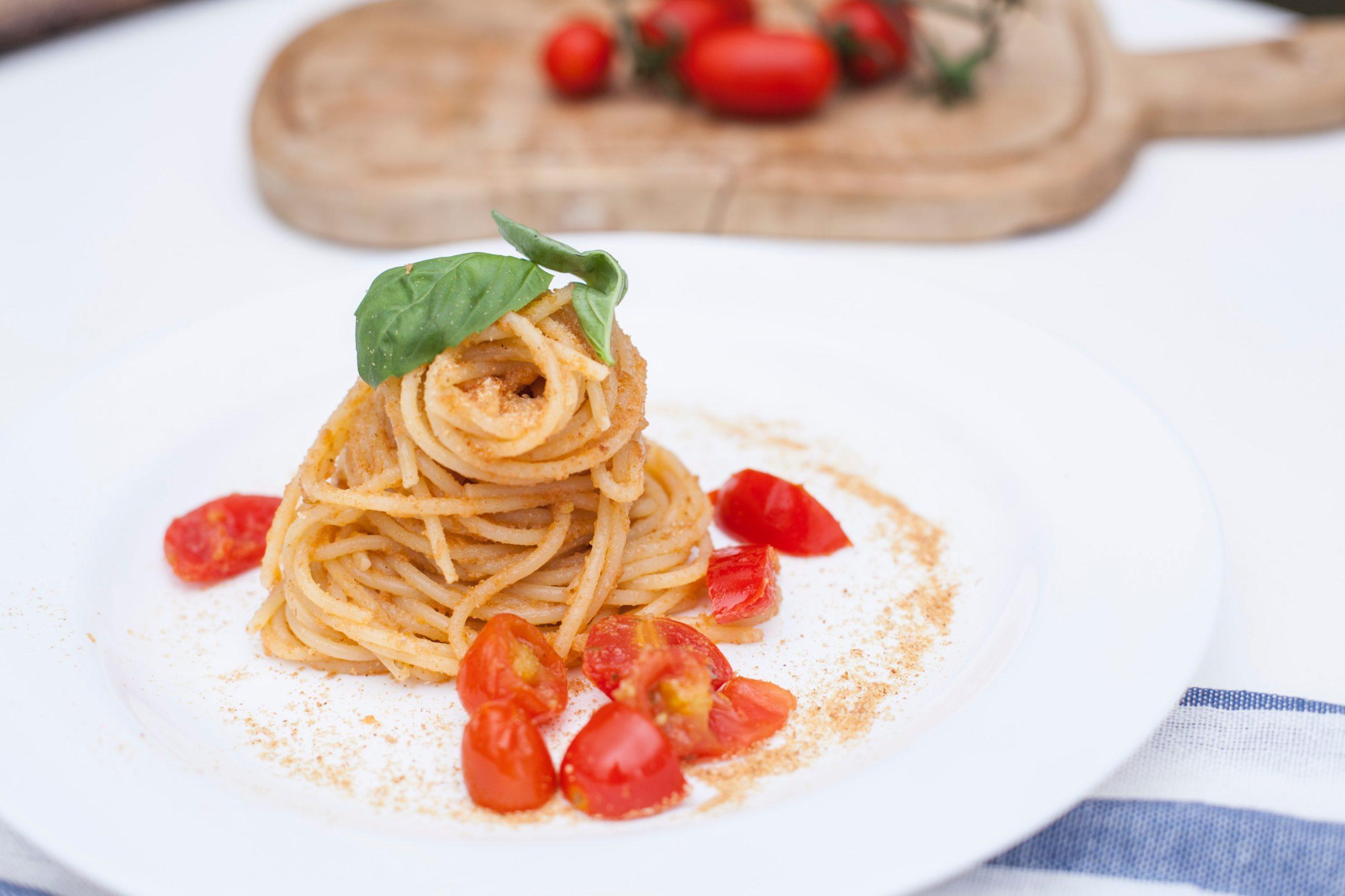 immagine con spaghetti artigianali, pomodorini e basilico fresco in foglie